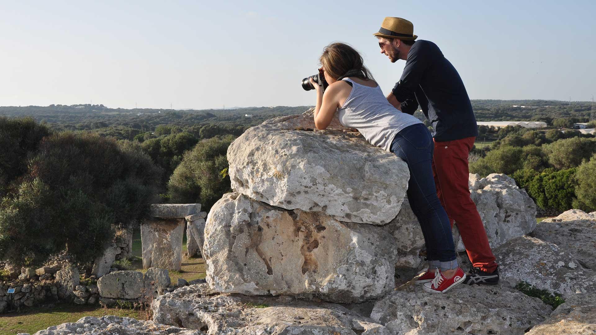 Pareja fotografiando un yacimiento arqueológico de Menorca.